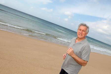 Senior man running on the beach photo