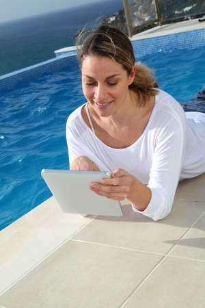 android tablet: Woman using electronic tablet by swimming pool Stock Photo