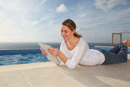 Woman using electronic tablet by swimming pool photo