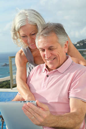 Senior couple at home using electronic tablet photo
