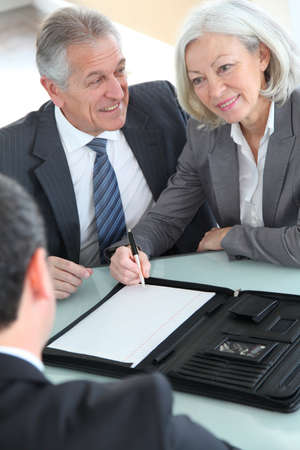 home purchase: Senior couple signing home purchase contract