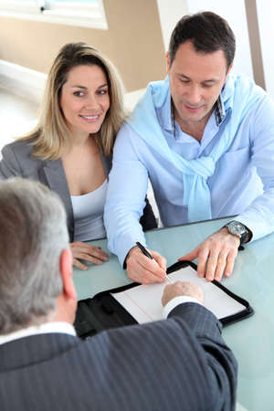 housing loan: Happy couple signing purchase contract with real-estate-agent Stock Photo