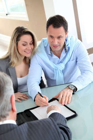 loans: Happy couple signing purchase contract with real-estate-agent Stock Photo