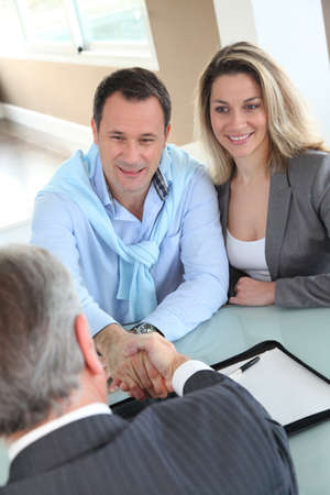 financial agreement: Happy couple signing purchase contract with real-estate-agent Stock Photo