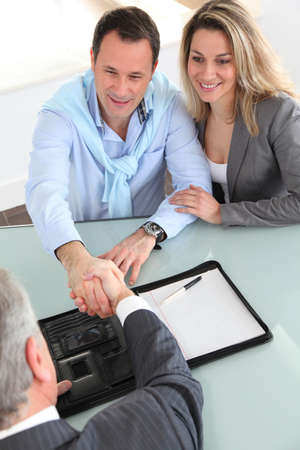 financial adviser: Happy couple signing purchase contract with real-estate-agent Stock Photo