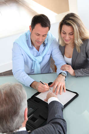 contract signing: Happy couple signing purchase contract with real-estate-agent Stock Photo