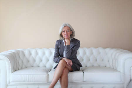 Senior woman in grey suit sitting in white sofa Stock Photo - 8742525