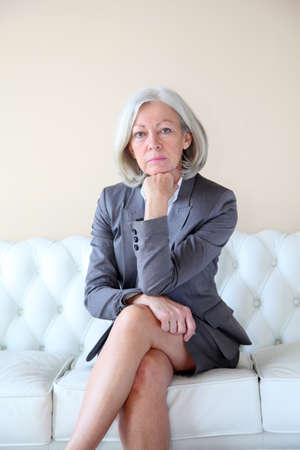 Senior woman in grey suit sitting in white sofa photo