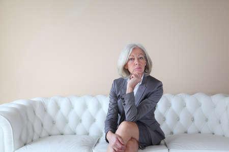 Senior woman in grey suit sitting in white sofa Stock Photo - 9031886