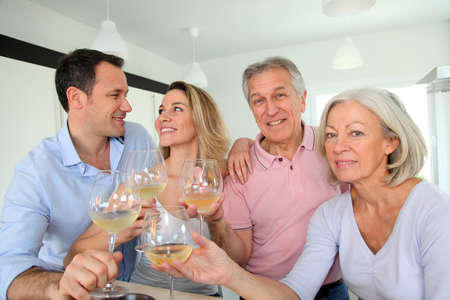 Family in home kitchen drinking wine photo
