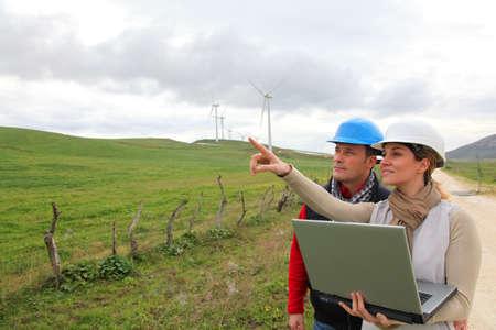 energy field: Engineers working by wind turbines field Stock Photo
