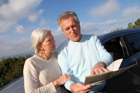 Senior couple looking at road map on car hood photo