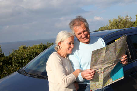 Senior couple looking at road map on car hood photo