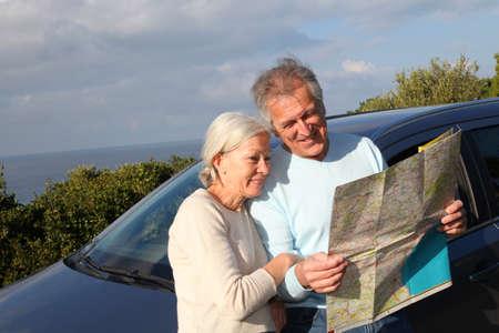 roadmap: Senior couple looking at road map on car hood Stock Photo