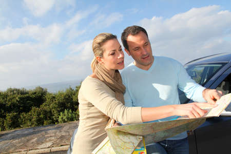 roadmap: Couple looking at road map on car hood