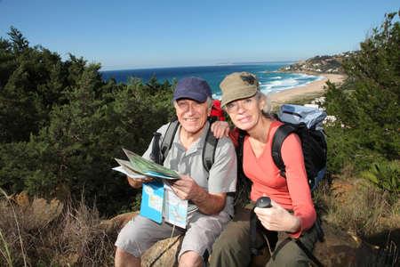 두서없는: Senior couple looking at map on a rambling day
