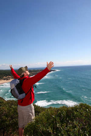 Hiker stretching arms up in front of the sea photo