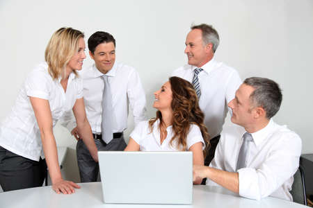 Group of office workers in front of laptop computer photo