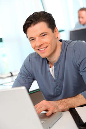 Portrait of office worker in front of laptop computer photo