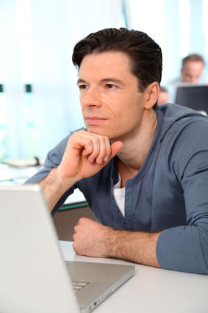 Office worker with exhausted look in front of computer photo