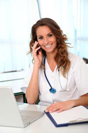 nurse uniform: Hermosa enfermera hablando por tel�fono m�vil Foto de archivo