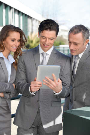 Business people meeting outside with electronic tablet photo