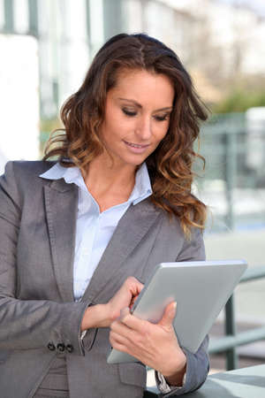 android tablet: Smiling businesswoman using electronic tablet outside Stock Photo