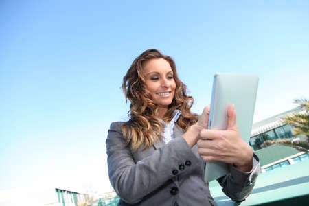 Smiling businesswoman using electronic tablet outside photo