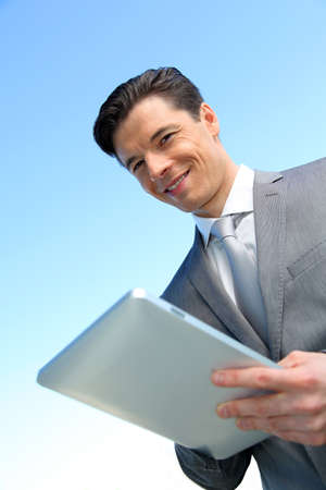 Portrait of businessman working on electronic tablet photo