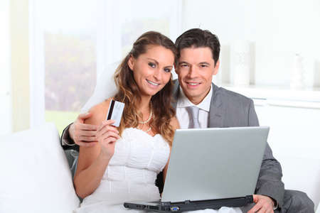 wedding gawn: Bride and groom doing shopping on inernet at home Stock Photo