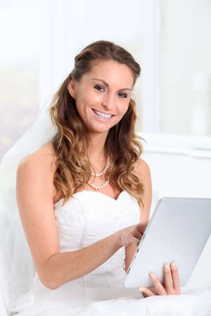 websurfing: Beautiful bride websurfing on electronic tablet Stock Photo