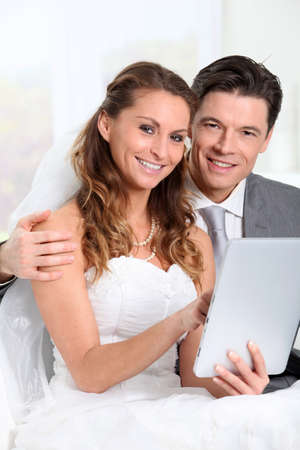 wedding gawn: Bride and groom using electronic tablet