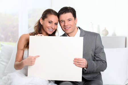 wedding gawn: Bride and groom holding whiteboard