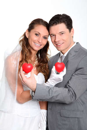 wedding gawn: Bride and groom holding red hearts on white background