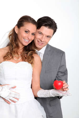 Bride and groom holding red hearts on white background