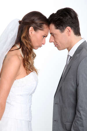 wedding gawn: Bride and groom standing on white background with upset look