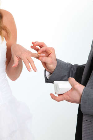Closeup of bride and groom exchanging wedding rings photo