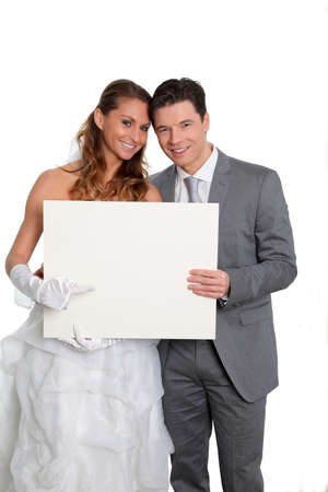 Bride and groom holding whiteboard  photo