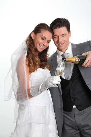 Bride and groom drinking champagne photo