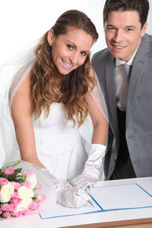Bride and groom signing marriage contract photo