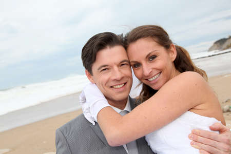 wedding gawn: Groom holding bride in his arms at the beach