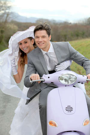 Married couple riding motorcycle on their wedding day