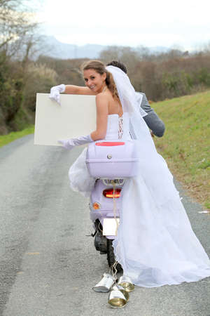 wedding gawn: Bride on a motorcycle ride holding whiteboard