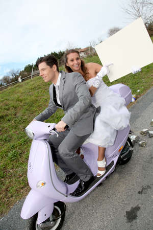 Bride on a motorcycle ride holding whiteboard photo