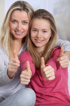 daughter mother: Portrait of mother and daughter with thumbs up Stock Photo