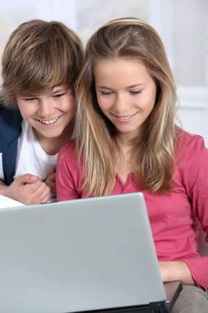 parental control: Brother and sister using laptop computer at home