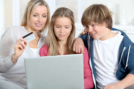 Mother and children at home doing online shopping photo