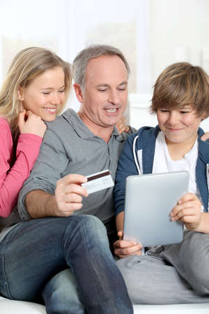 secured payment: Father and children doing online shopping at home Stock Photo
