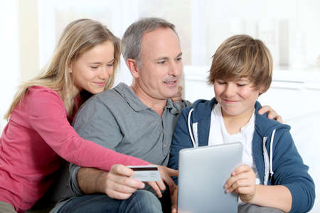 Father and children doing online shopping at home photo