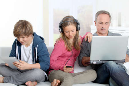 Father and children using electronic devices at home photo